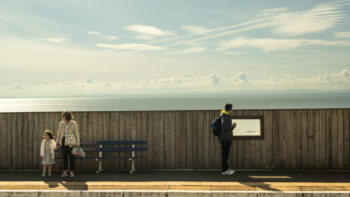 Passengers wait for a train at Kinghorn Station in Scotland. Perched high on a cliff, the platform feels as if it's floating above the ocean | photo by P.M.Lydon