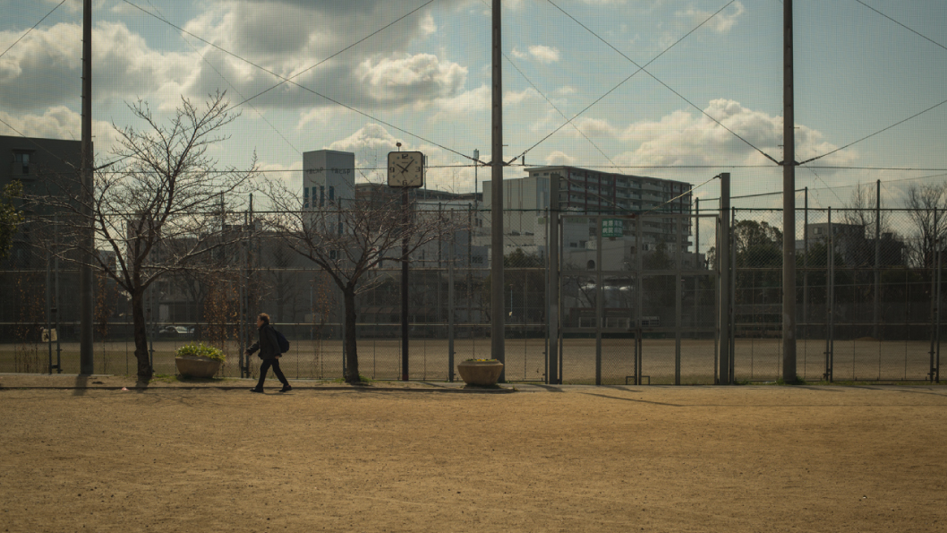 A woman walks past a community baseball field in a suburb of Osaka, Japan | photo by P.M.Lydon