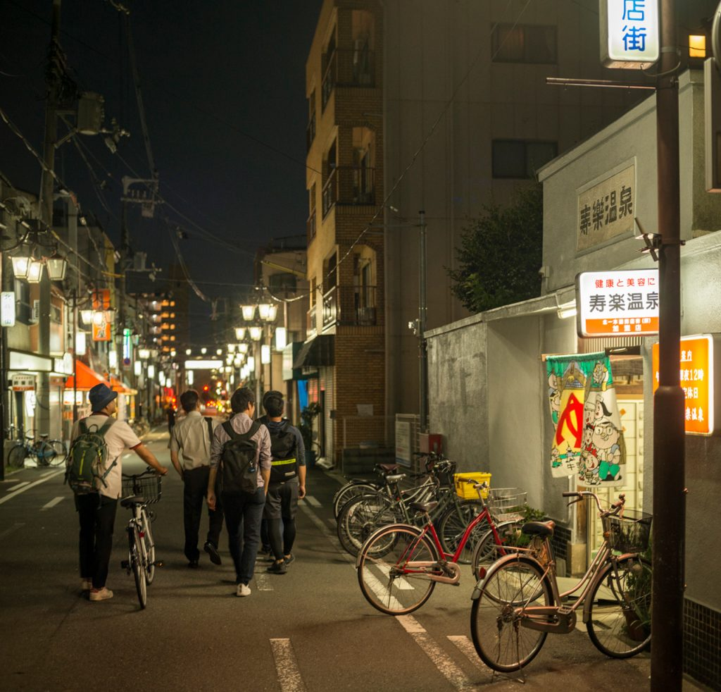 A group of young men walk by Juraku, an old community bath house, still lit up and in use in Kitakagaya, Osaka, Japan