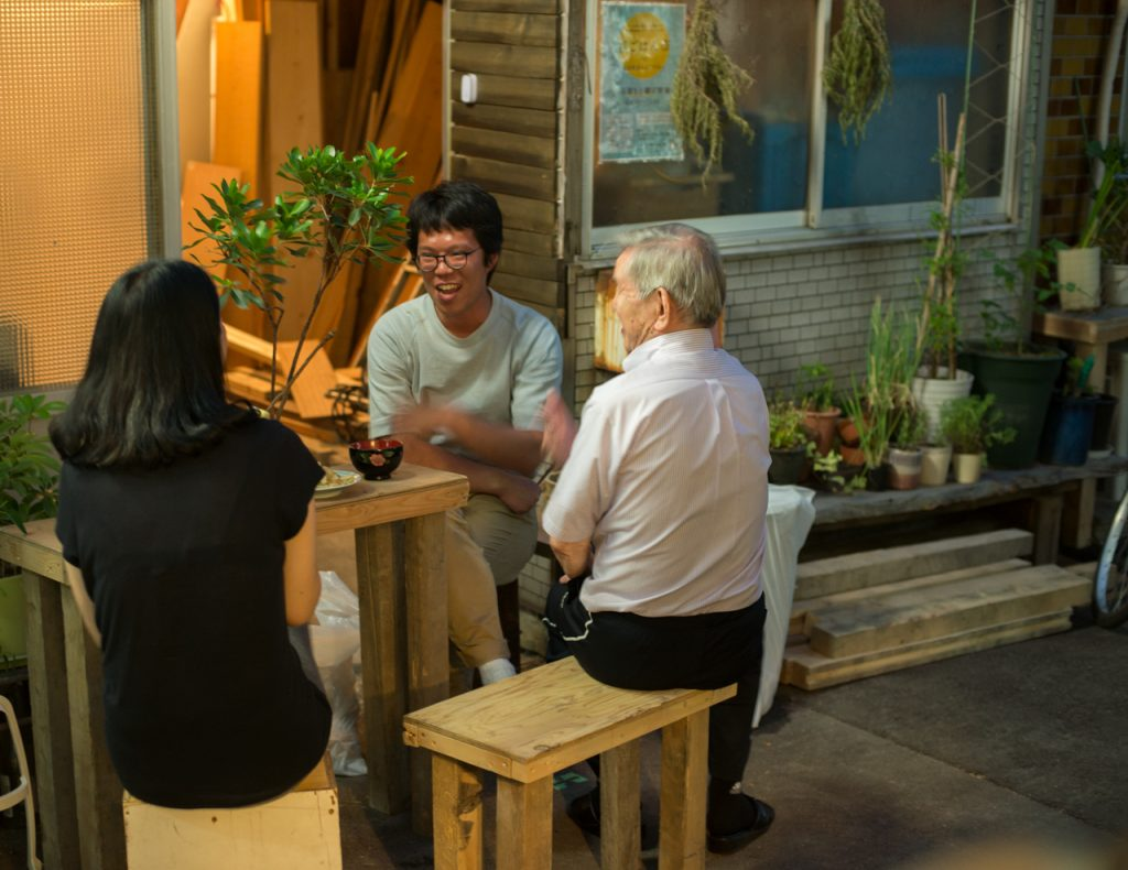 Neighbors enjoy food and drink outside a home in an alleyway in Osaka, Japan