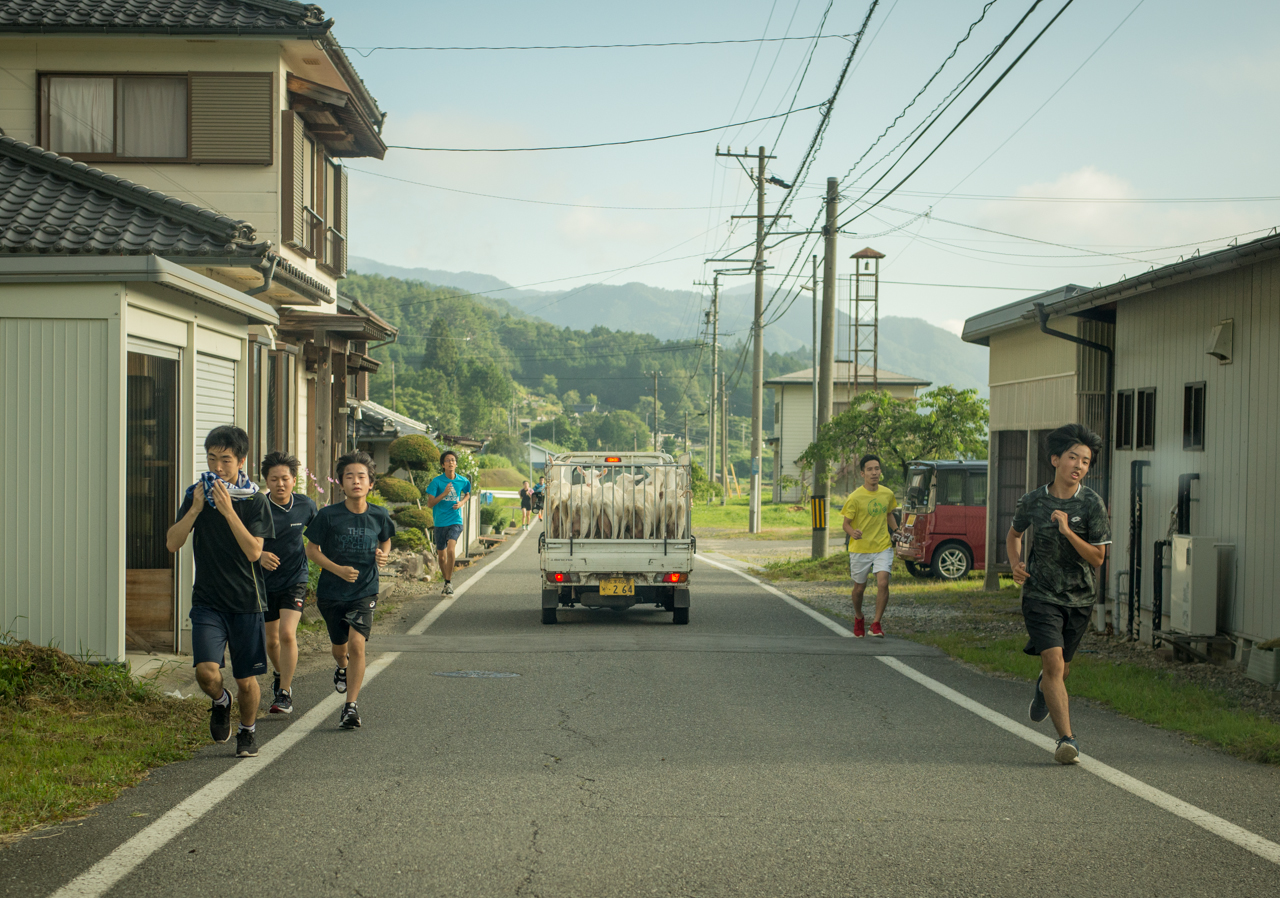 A group of young runners pass a truck of goats on their daily practice route through Urugi Village