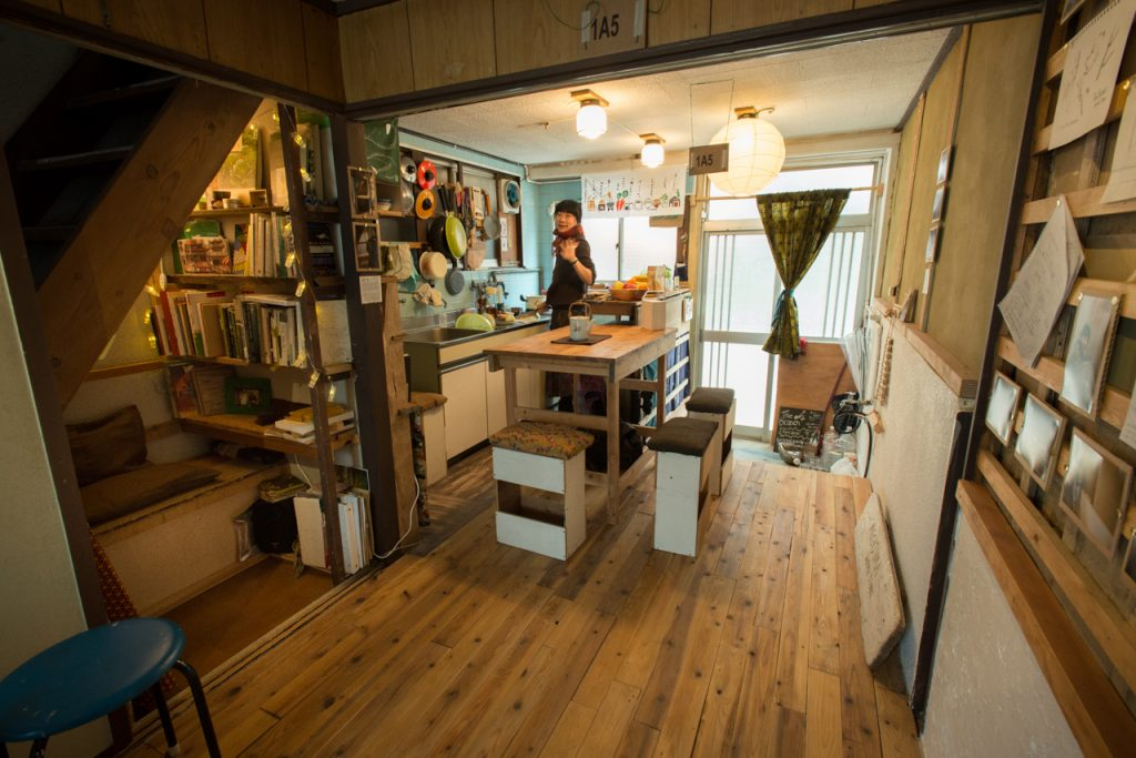 A warm looking home with wood floors and a woman in the kitchen
