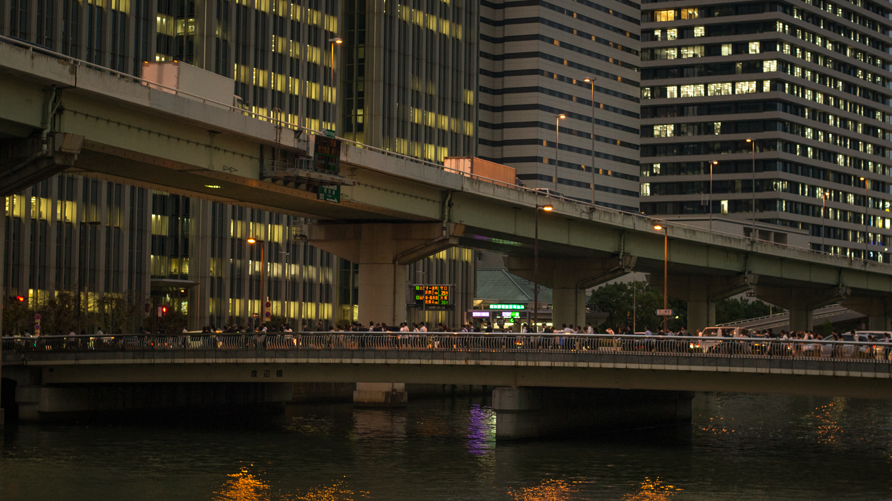 A wall of office buildings and a bridge with office workers walking across in Osaka, Japan.
