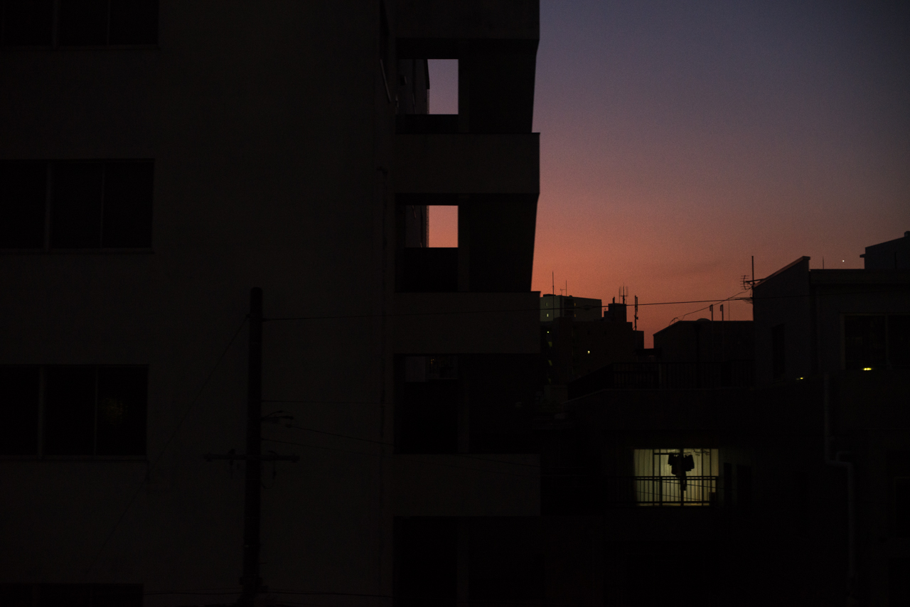 The dark blocks of Nagoya's cityscape frame a bright orange and purple sunset and a single small window with it's light on, and laundry hanging to dry.