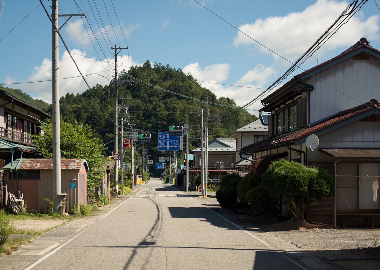 The main street of Urugi Village, with its two traffic lights and a small mountain in the background.