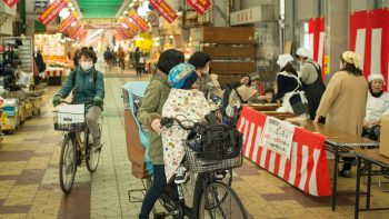 A mom and child stop on their bicycle, in front of a red bean soup stand on the Kagaya shopping street in Osaka, Japan / image: Patrick M. Lydon
